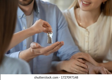 Close up of male real estate agent give keys to new house to excited young couple buyers at meeting, woman realtor or broker congratulate happy millennial husband and wife with home buying or renting