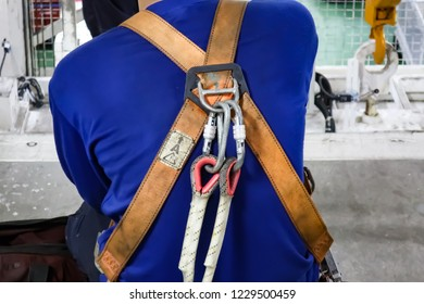 Close up of male rope access job industrial worker, using a safety device descender for repairing roof of the factory.