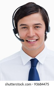 Close up of male telephone support employee with headset on against a white background