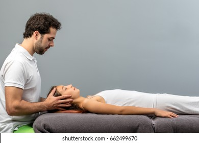 Close up of male therapist doing reiki therapy on little girl touching head on both sides.