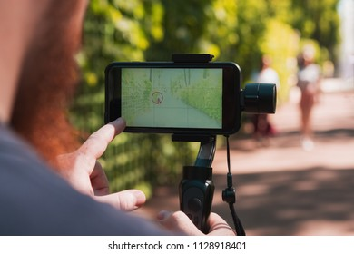 Close up male traveler  records video and photo on smartphone using image stabilizer.