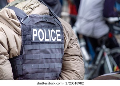 A close up of a male undercover police officer stands on a street among a crowd of people. The officer has a black canvas bullet proof vest on with the word police spelled out in white letters.