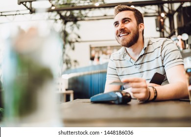 close up of male using credit card contactless technology and smartphone for paying in restaurant