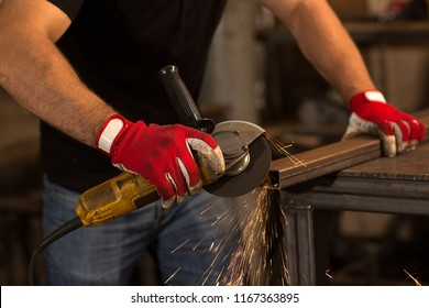Close up of male worker, wearing in special protective gloves, making cuts on square iron pipe with electric grinder, sparks flying during working with steel at workshop. Dangerous work concept.