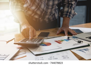 Close up of a man accountant working on calculator to calculate business data, accountancy document and laptop computer at office, business financial concept