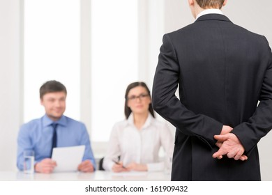 Close up of man back with fingers crossed behind. Idea of lying on job interview
