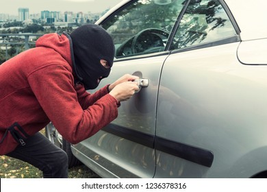 Close up of man in black robber mask breaking the car lock on a city background. Ill-intended thief forces the vehicle lock with a picklock. Evil-doer encroaches a parked automobile. Criminal attempt.