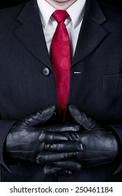 Close up of man in black suit, red tie and leather gloves.