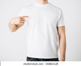 close up of man in blank t-shirt pointing at himself