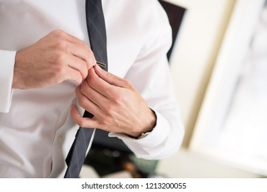 71b6810ade79 Close up of man by a window getting ready and fastening a black tie clip  before