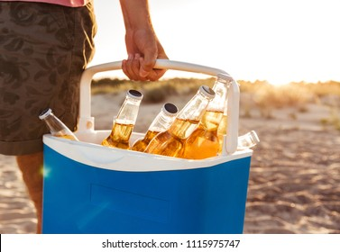Close up of man carrying beer bottles in an icebox at the beach
