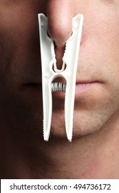 Close up of a man with a clothespin on his nose