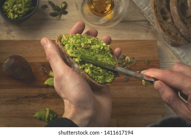Close up of a man cook hands making avocado sandwich on a wooden table. Healthy food preparation