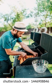Close up of man cooking on grill,  having beers and cooking on garden barbecue. Lifestyle, leisure concept