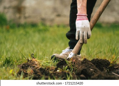 Close up man digs soil with metal shovel. Digging ground for plant seeding. Agriculture concept. Worker in gloves. Copy space. Vertical orientation