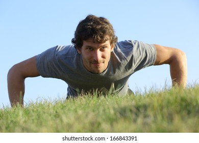 Close up of a man doing pushups on the grass with the horizon in the background