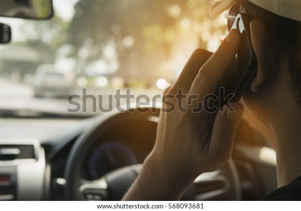 Close up of a man driving car dangerously while using mobile phone