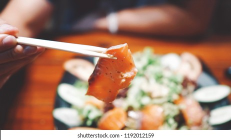 Close up man eating fresh salmon salad (Japanese food) in Japanese restaurant. Healthy food, selective focus