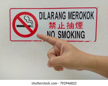 Close up of man finger pointing on No Smoking sign