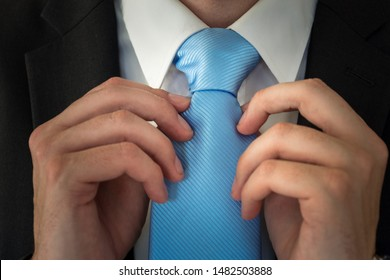 close up of a man fixing his tie knot. blue tie and white shirt