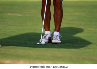 Close up man goft player with detail shoe putter ball and shadow on green.