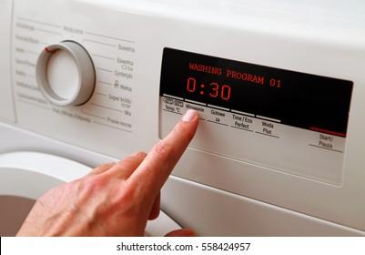 Close up of man hand adjusting washing machine