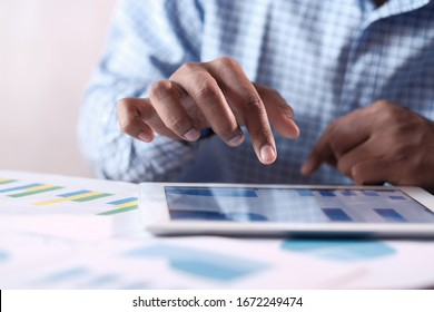 Close up of man hand analyzing chart on digital tablet
