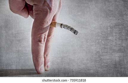 close up man hand with burning cigarette as penis in smoking cause sexual erectile dysfunction and impotence warning concept isolated on grunge background