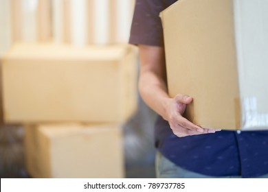 close up man hand carrying big box for move from old to new home or residence