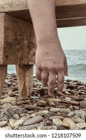 Close up man hand hanging from a beach bench, pebbles and sea on background. Atmosphere of total exhausting, prostrate, solitude, loneliness. Outdoors, copy space.