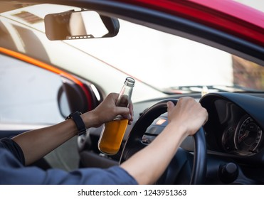 close up of Man hand holding alcohol bottle already driver and drinking alcohol from a bottle as a driving the car,dangerous concept