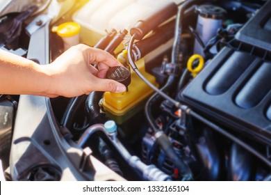 close up of man hand holding cap of  power steeling  fluid reservoir tank , in car service shop
