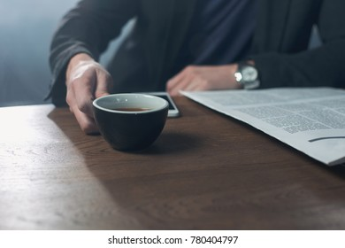 Close up man hand holding cup of delicious tea while sitting at table. Relax and business concept. Copy space