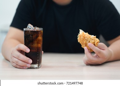 close up man hand holding glass of cola with fried chicken,unhealthy lifestyle concept