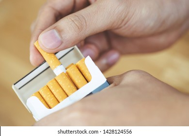 close up man hand holding peel it off cigarette pack prepare smoking a cigarette. Packing line up. photo filters Natural light.