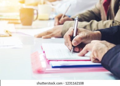 close up of a man hand holding pen and writing on note book on white table while meeting with his team worker