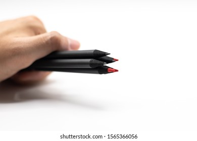 close up man hand holding the pencils black and red on white background. for concept design