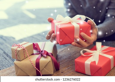 close up man hand holding red gift box for with special of snow falling and blinking star at living room house in merry christmas and happy new year festival celebrate concept