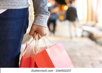 Nahaufnahme Hand, die eine rote Einkaufstasche hält, während sie an der Außenstrasse spazieren geht, um sie verkaufsfördernd am Boxtag, am Weihnachtsfest, in der Wintermode-Sammlung und beim fröhlichen Neujahrskonzept zu verkaufen