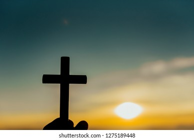 Close up man hand holding wood cross or religion symbol shape over a sunset sky with clouds background for God,Christianity, religious, faith, holy, spiritual, Jesus, belief or resurrection.