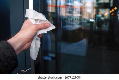 ナプキンを通してドアの取っ手を持つ男性の接写。covid-19の世界的流行の際に、公共の場での表面への接触から保護。検疫のコンセプト