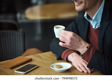 Close up man hand keeping mug of delicious coffee. He tasting it while sitting at table in confectionary shop. Rest concept