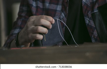 Close up of man hand leather maker holding wallet of blue color and sewing