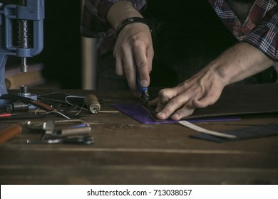 Close up of man hand leather manufacturer performs work on table with tools
