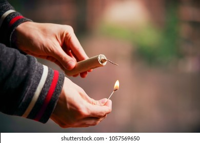 Close up of man hand lighting up a firecrackers in a burred background