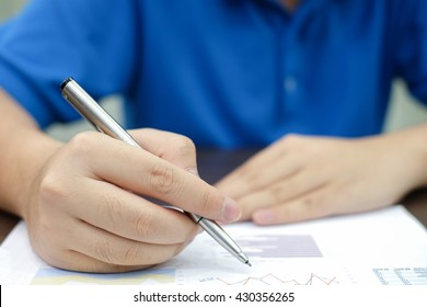 close up man hand with pen proof report document on paper application concept.