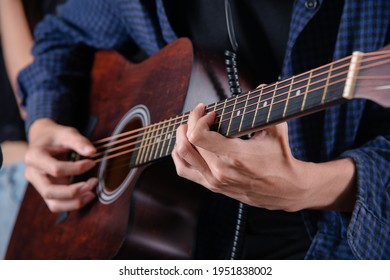 close up of man hand playing acustic guitar
