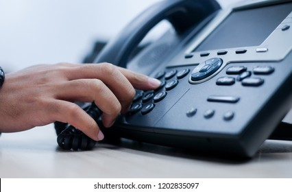 close up man hand point to press button number on telephone office desk. hotline employee concept