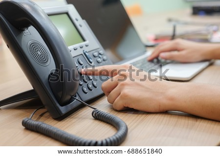close up man hand pointing try to press button number on telephone office desk.multitasking employee concept