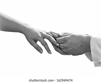 Close up of man hand putting a wedding ring on the bride finger isolate on white background, Black and white photography